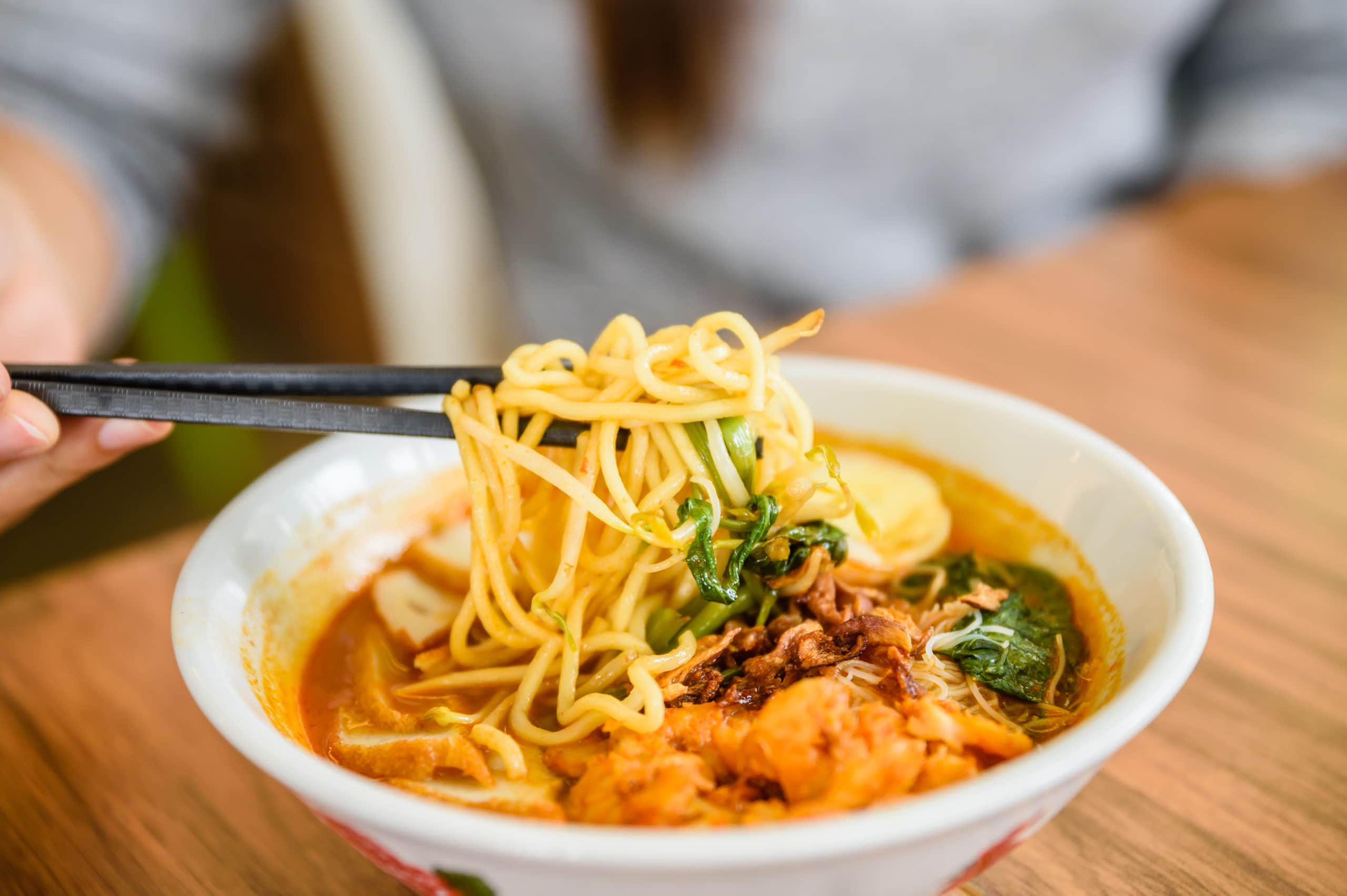 Hand with Chinese chopsticks eating noodle, a famous Malaysia prawn noodle cerry soup.