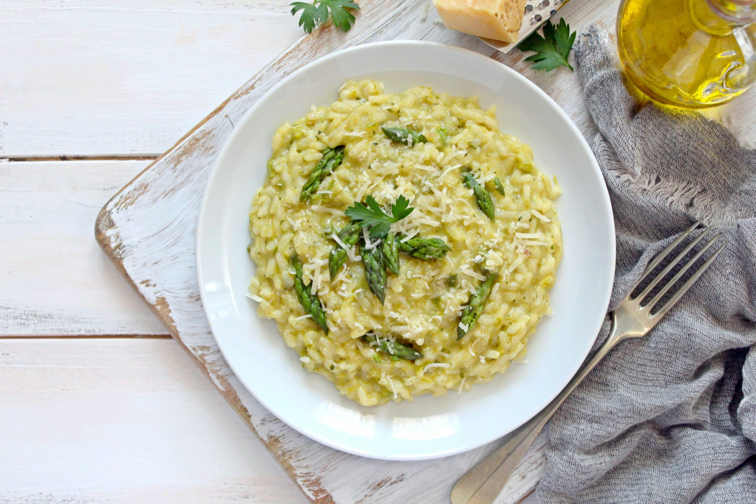Italian Risotto With Spring Asparagus And Parmesan Cheese In Plate On Light Background. Top View With Copy Space.